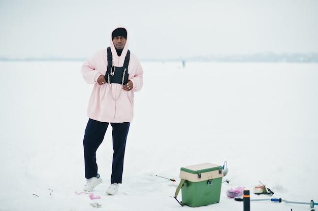 Pescatore afroamericano sul mare congelato. pesca invernale.