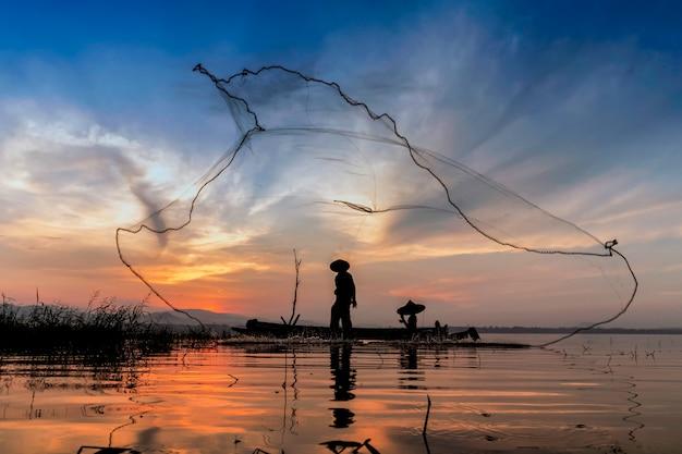 Pescatore al mattino con barche di legno, vecchie lanterne e reti