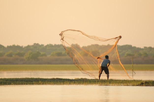 Pescatore che getta una rete nel lago