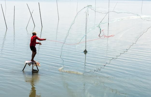 Pescatore che lancia la rete nella palude