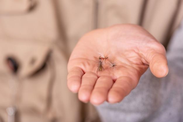 Pescatore che mostra la palma della mano del gancio della mosca di pesca.