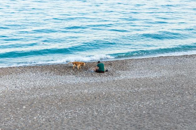 Pescatore con cane sulla spiaggia del bosforo