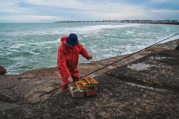 Pescatore con scatola per attrezzatura da pesca.