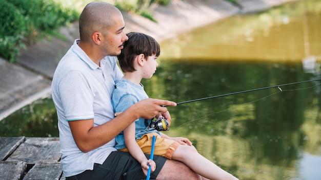 Pescatore con suo figlio pesca sul lago