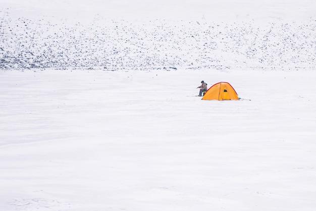Pescatore con una tenda su un lago ghiacciato