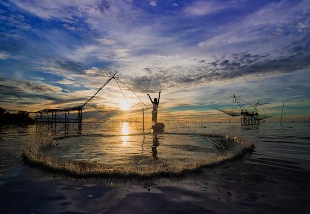 Pescatore della tailandia che getta il pesce della cattura della rete da pesca che causa la spruzzata dell'acqua