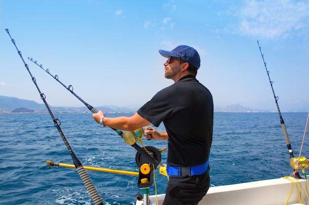 Pescatore di mare blu in barca da pesca a traina con downrigger