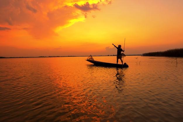 Pescatore di sagoma con il tramonto