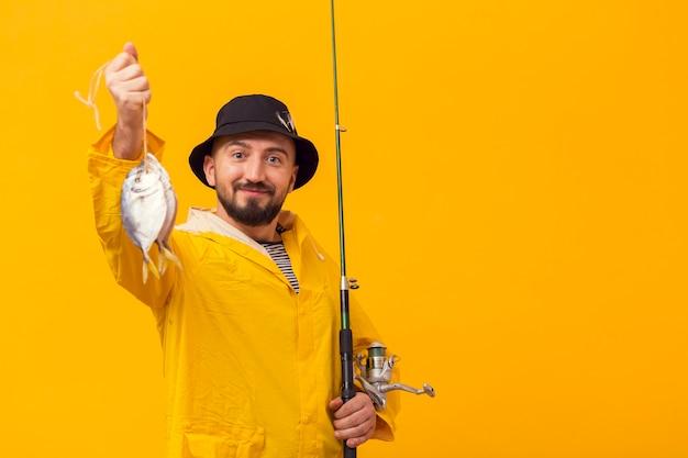 Pescatore fiero che tiene cattura e canna da pesca