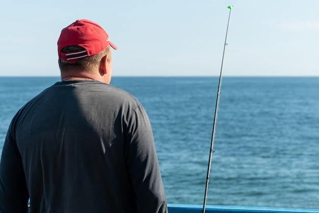 Pescatore pesca dal molo