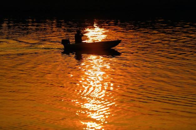 Pescatore pesca dalla barca sul lago al tramonto