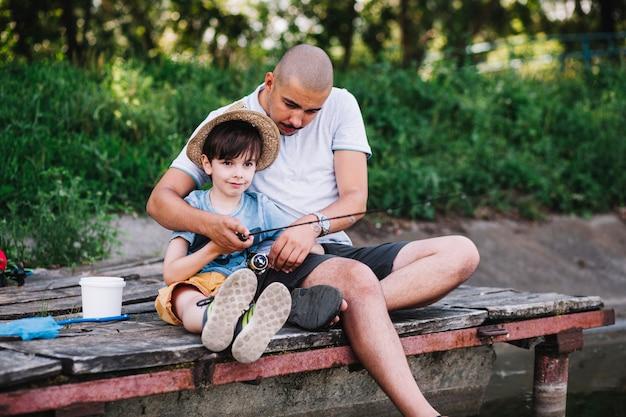 Pescatore seduto sul molo con suo figlio pesca sul lago