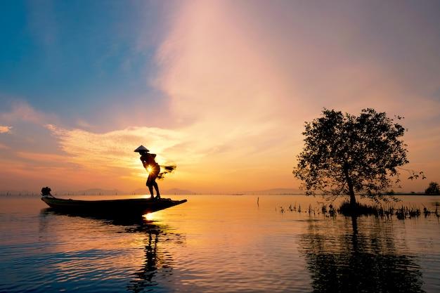 Pescatore sulla barca cattura pesci con sunrise