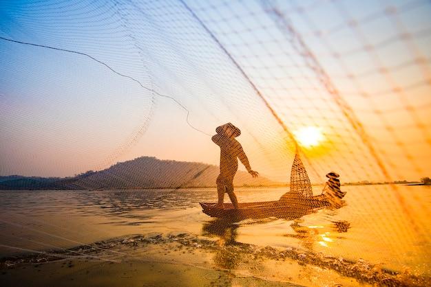 Pescatore sulla rete del tramonto asia del fiume della barca facendo uso sul tramonto o sull'alba di legno della rete da colata della barca