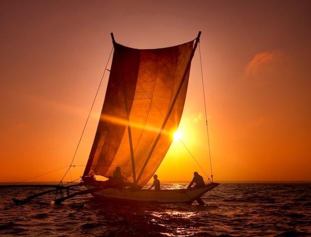Pescatori su un catamarano al tramonto. sri lanka