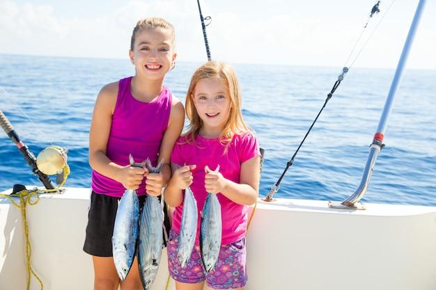 Pescatrici di tonno felice scherzano le ragazze con i pesci catturati