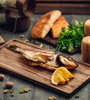 Pesce affumicato su una tavola di legno con una fetta di limone