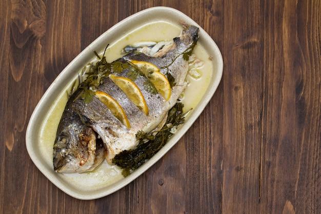 Pesce al forno con limone sul piatto