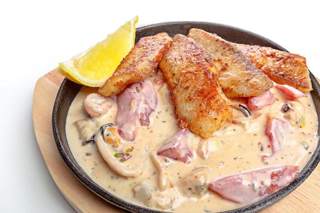 Pesce al forno in una pentola isolata su bianco