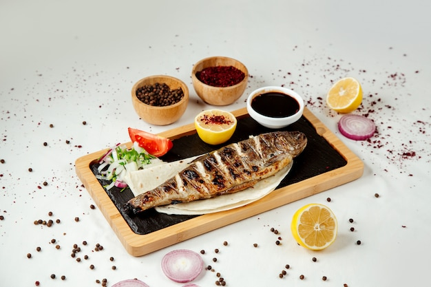 Pesce alla griglia con cipolla e salsa su una tavola di legno