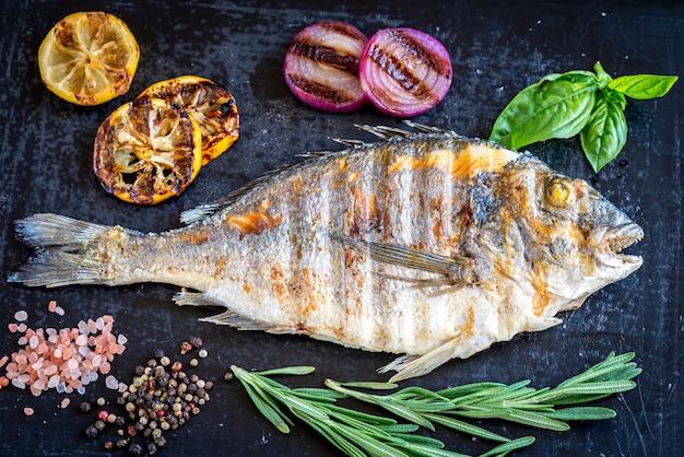 Pesce alla griglia dorada con verdure ed erbe