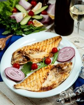 Pesce alla griglia tagliato a metà servito con cipolla e pomodorini