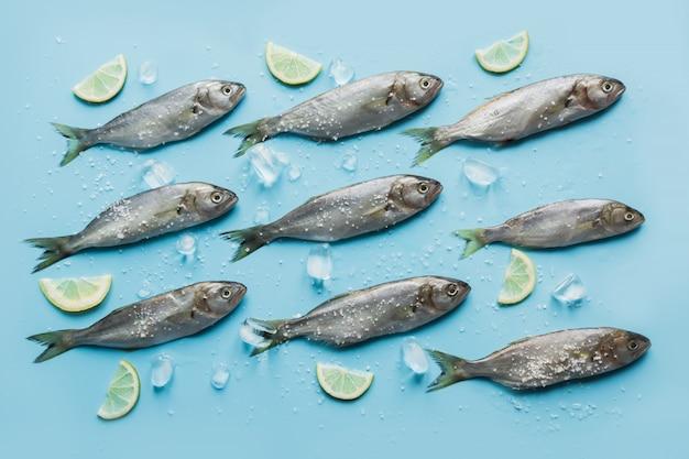 Pesce azzurro con limone, sale marino, limone sul blu pastello.