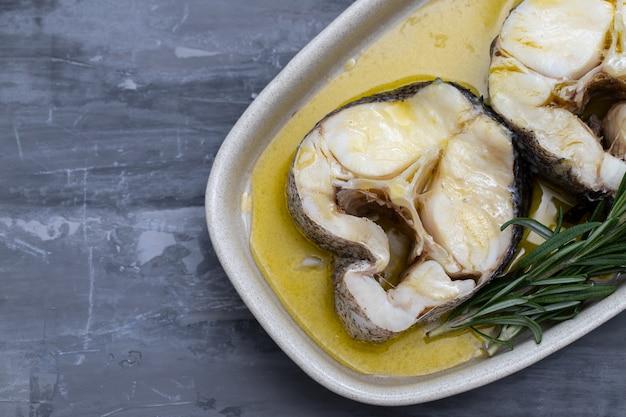 Pesce bollito con olio d'oliva e rosmarino nel piatto