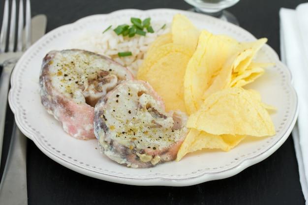 Pesce bollito con riso e patatine fritte sul piatto