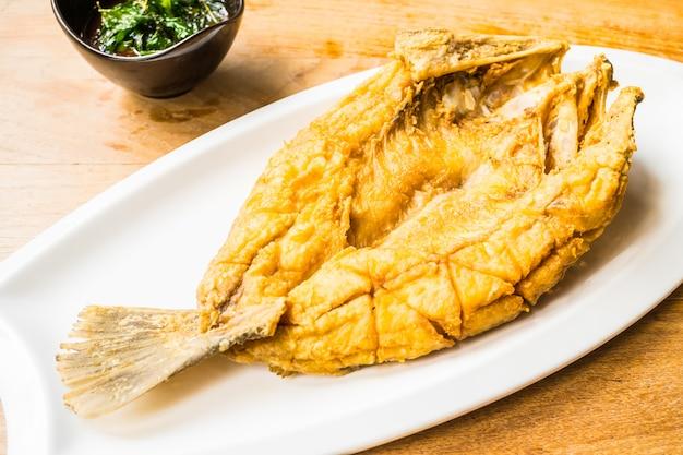 Pesce branzino fritto in piatto bianco con salsa piccante e dolce