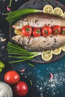 Pesce con erbe, limone e pomodori in un piatto rustico