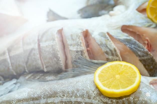 Pesce congelato e limone giallo su ghiaccio,