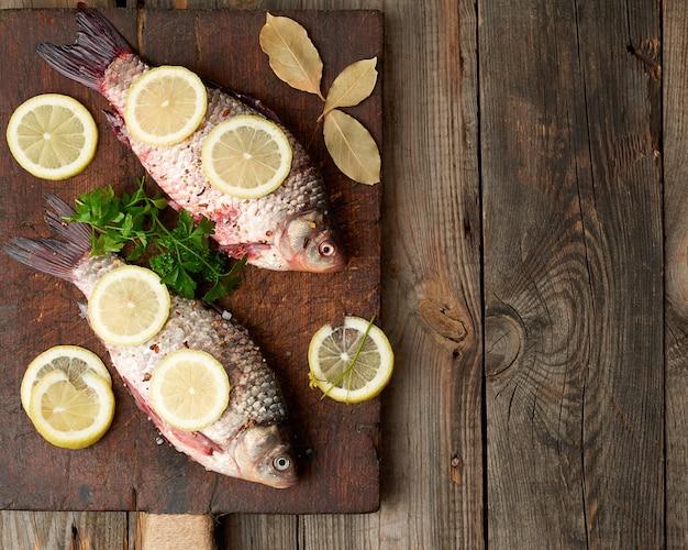 Pesce crucian fresco cosparso di spezie e fette di limone e si trova su un tagliere di legno marrone