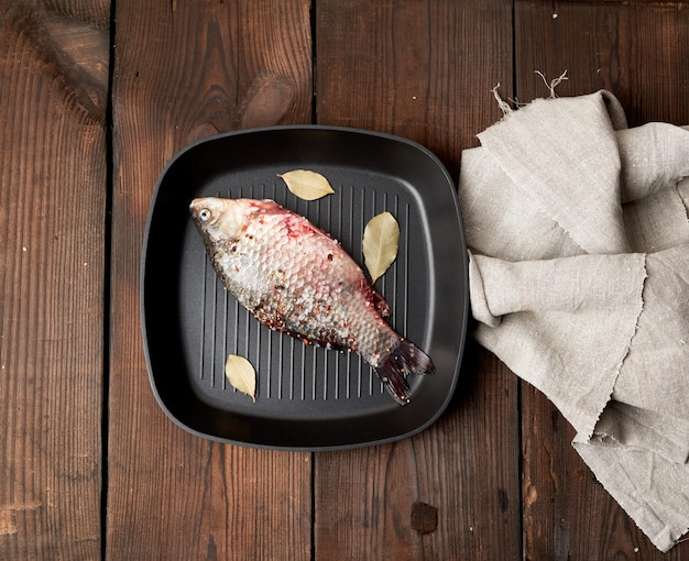 Pesce crucian fresco cosparso di spezie e giace in una padella quadrata nera