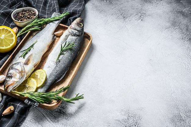 Pesce crudo del branzino con le erbe e limone sulla tavola bianca