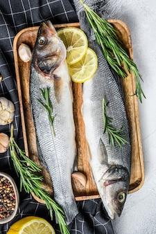 Pesce crudo del branzino con le erbe e limone sulla tavola nera.