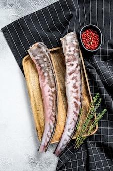 Pesce crudo dell'anguilla con gli ingredienti di cottura. sfondo grigio. vista dall'alto
