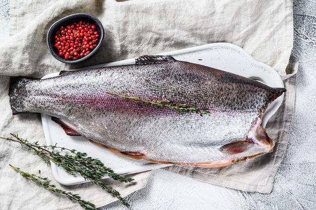 Pesce crudo della trota iridea con sale e timo. sfondo grigio.