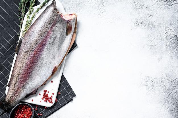 Pesce crudo della trota iridea con sale e timo. superficie grigia. vista dall'alto. copia spazio