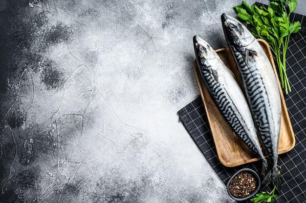 Pesce crudo dello sgombro con prezzemolo e pepe. frutti di mare freschi sullo sfondo