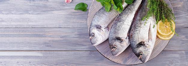 Pesce crudo di dorado con le erbe verdi che cucina sul tagliere. banner. vista dall'alto
