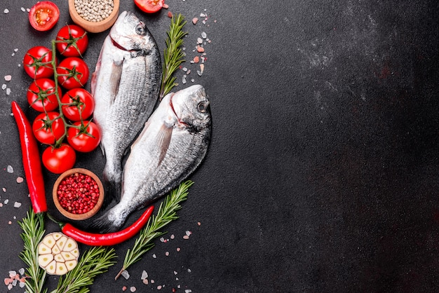 Pesce crudo di dorado con le spezie che cucinano sul tagliere. dorado di pesce fresco. dorado e ingredienti per cucinare su un tavolo
