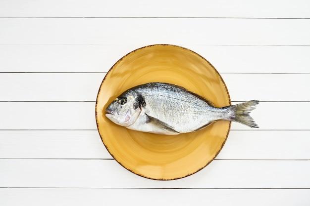 Pesce crudo di dorado sul piatto giallo sulla tavola di legno bianca. vista dall'alto, copia spazio