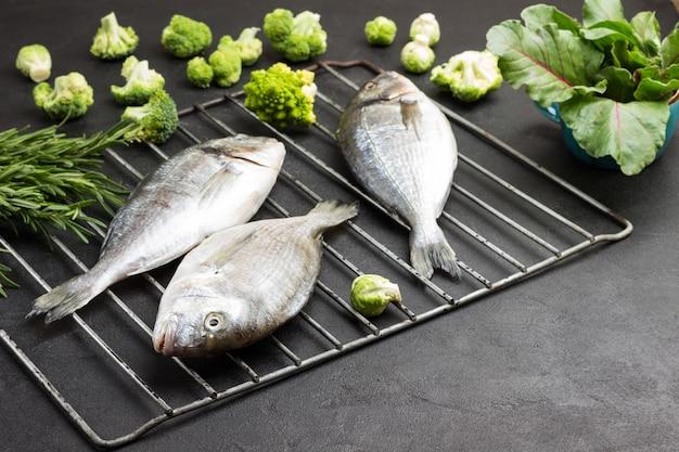 Pesce crudo di dorado sulla griglia della griglia del metallo con verdure verdi e vegetazione.