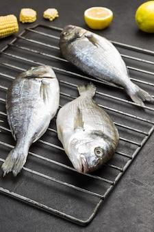 Pesce crudo di dorado sulla griglia della griglia del metallo. mais e limone sul nero