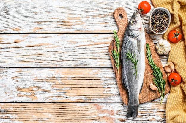 Pesce crudo fresco del branzino con le erbe sulla tavola bianca.