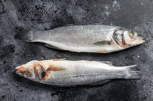 Pesce crudo fresco del branzino sulla tavola nera.