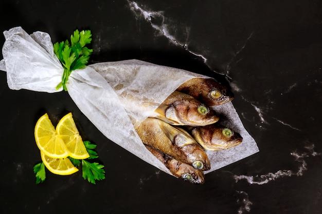Pesce crudo fresco sano sul bordo nero con limone e prezzemolo avvolti in carta pergamena.