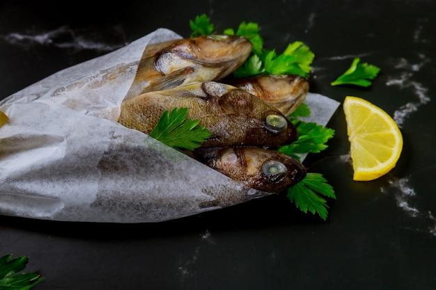 Pesce crudo fresco sano sul bordo nero con limone e prezzemolo.