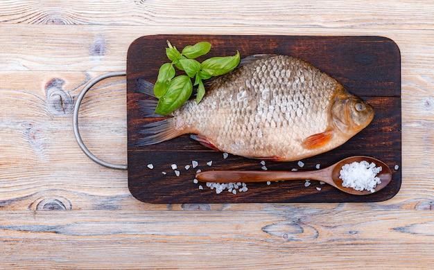 Pesce crudo fresco su un fondo di legno scuro. orata e spezie. foglie di basilico verde, sale marino, cucchiaio di legno.